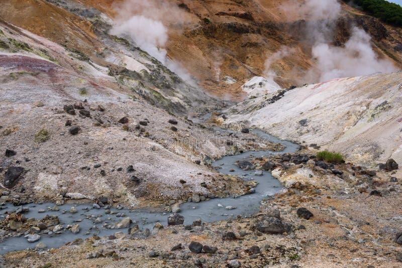 El pequeño río fluye a través de las rocas del valle Jigokudani del infierno foto de archivo