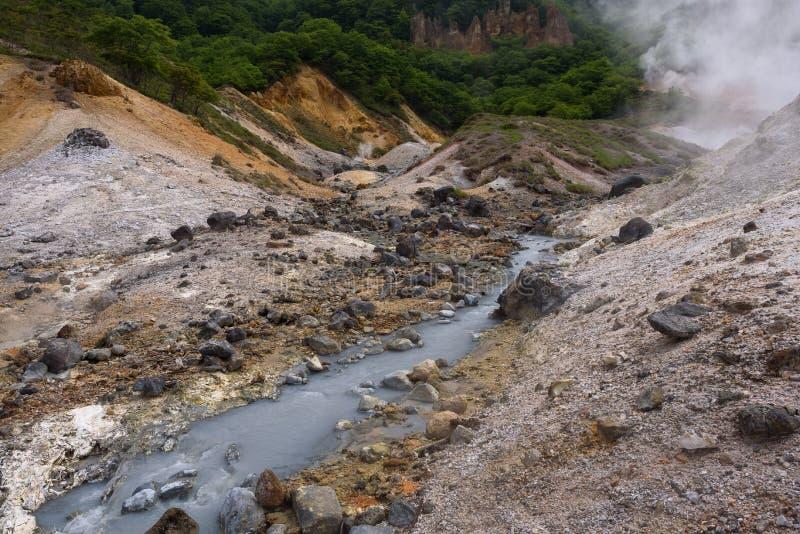El pequeño río fluye a través de las rocas del valle Jigokudani del infierno imagen de archivo