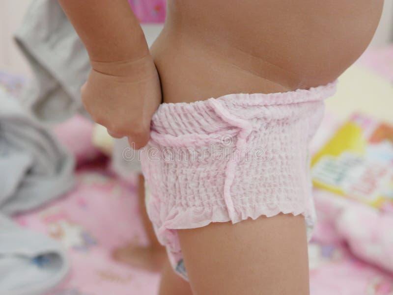El pequeño ` s del bebé da poner un pañal sola imagen de archivo