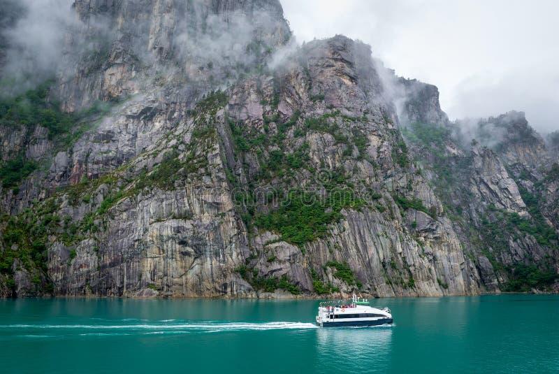 El pequeño transbordador en el fiordo hermoso con las orillas rocosas y el tourquise riegan fotografía de archivo libre de regalías