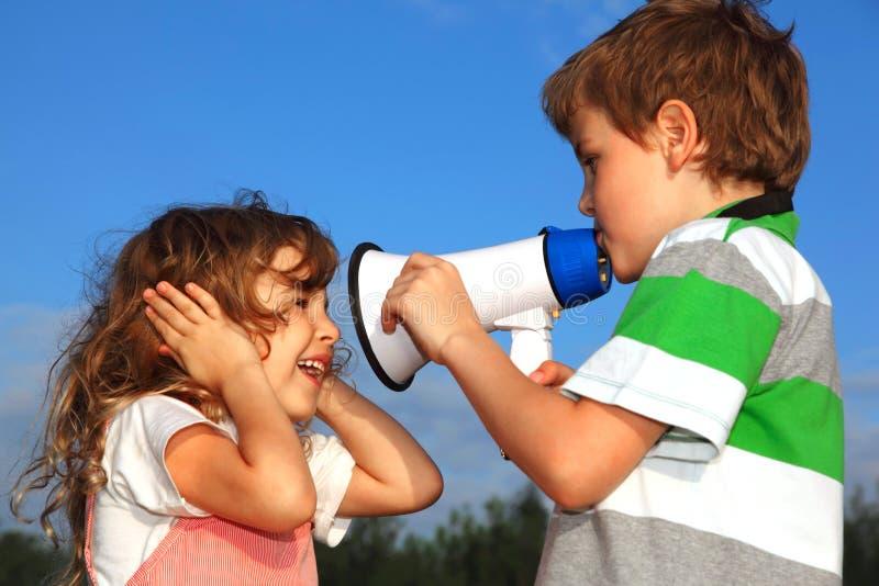 El pequeños muchacho y muchacha juegan con el altavoz imágenes de archivo libres de regalías