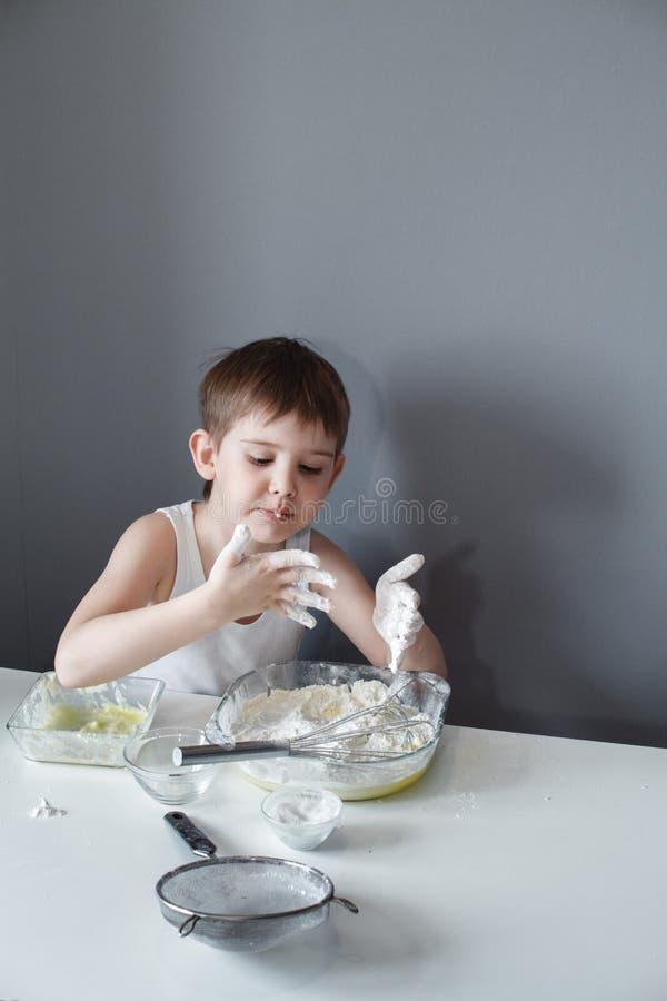 El peque?o ni?o alegre hace la torta dulce A?ade la harina a la pasta El sentarse en una tabla blanca en un fondo gris Preparaci? foto de archivo