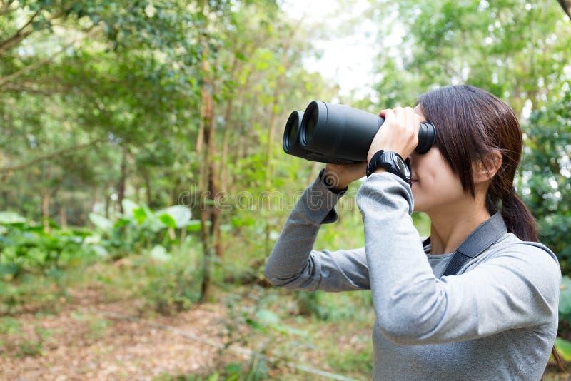 El perfil lateral de la mujer que mira sin embargo binocular foto de archivo libre de regalías