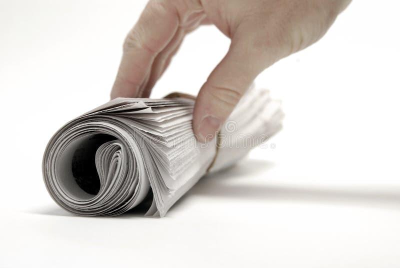 El periódico rodó para arriba aislado en el blanco para las noticias y la mano imagenes de archivo