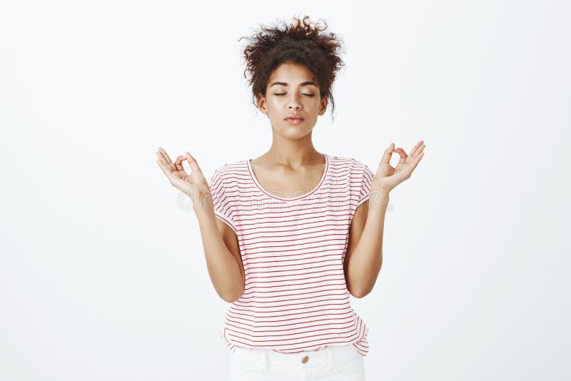 El permanecer calma y relajado en atmósfera urbana Mujer de piel morena resuelta linda en camiseta rayada, ojos de cierre y foto de archivo libre de regalías