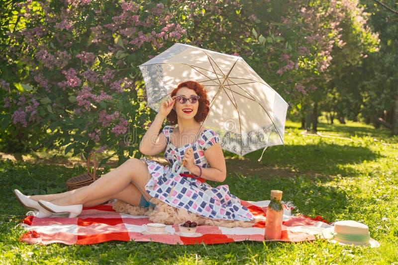 El perno feliz pelirrojo encima de la muchacha en vestido del verano del vintage y de medias clásicas con una costura en la parte fotos de archivo libres de regalías