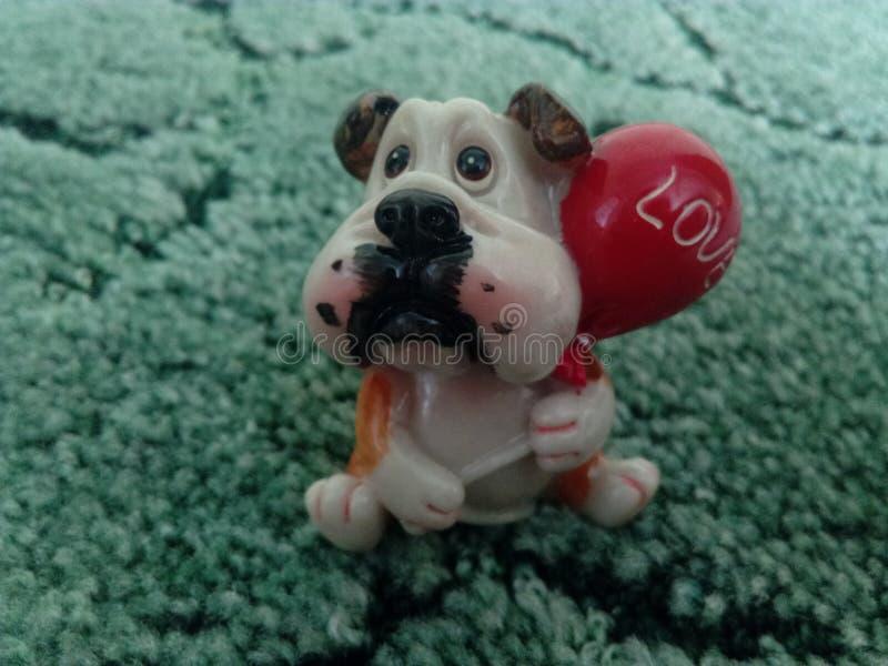 El perrito lindo le ama que se sienta en fondo verde imagen de archivo libre de regalías