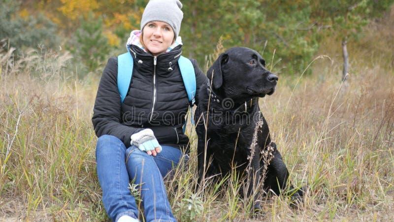 El perro negro se sienta al lado de su casera y mira la otra manera foto imágenes de archivo libres de regalías