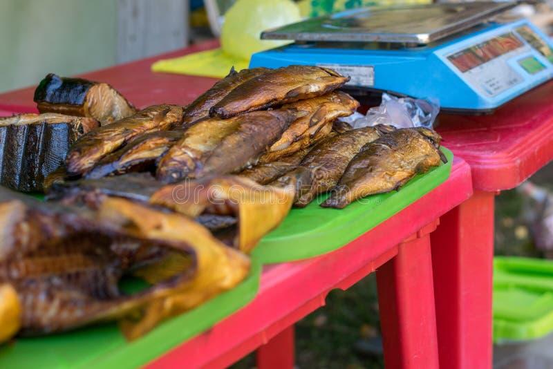 El pescado secado, ahumado miente en el mercado del pueblo en el contador, al lado de las escalas fotografía de archivo