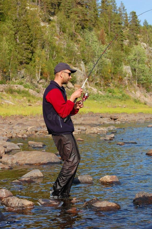 El pescador coge un salmón en el río del norte imagen de archivo libre de regalías