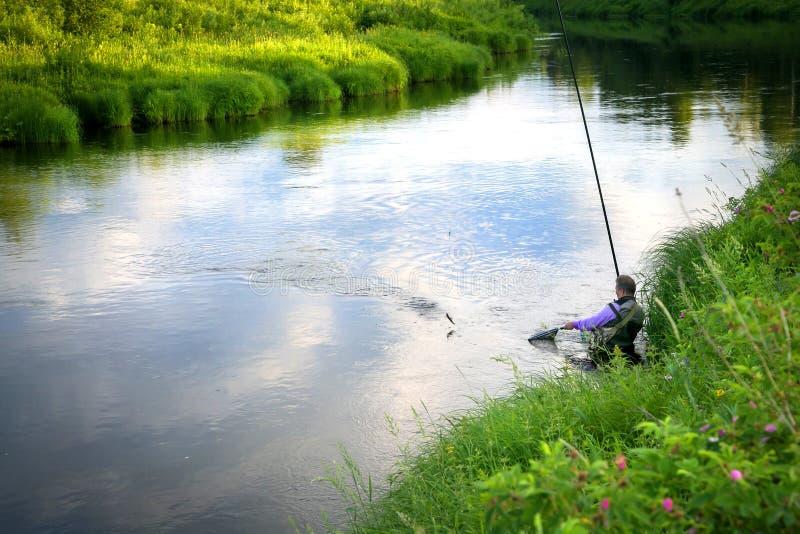 El pescador cogió pescados en el río en el campo fotos de archivo