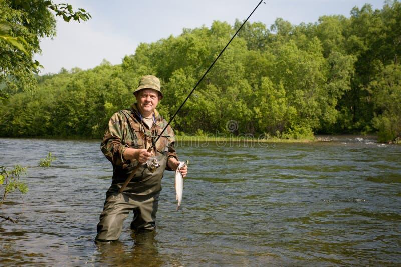 El pescador cogió un salmón foto de archivo