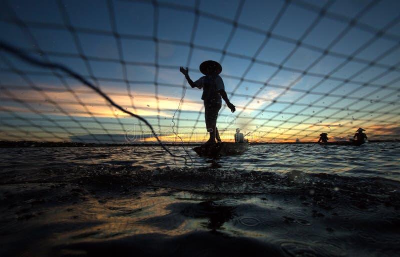 El pescador de la silueta es red de pesca imagenes de archivo