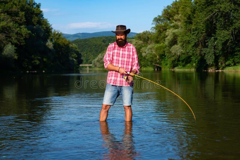 El pescador del hombre coge un pescado Pesca de mosca en aguas tranquilas Trucha de Brown que es cogida en red de pesca Pesca del fotos de archivo libres de regalías
