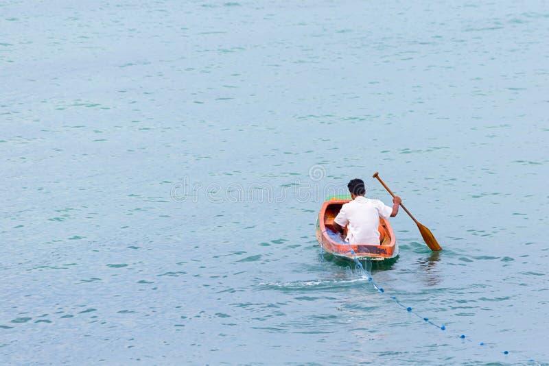 El pescador en flotadores de un bote pequeño en el océano del agua echa el espacio de la copia del pueblo pesquero del paseo del  imágenes de archivo libres de regalías