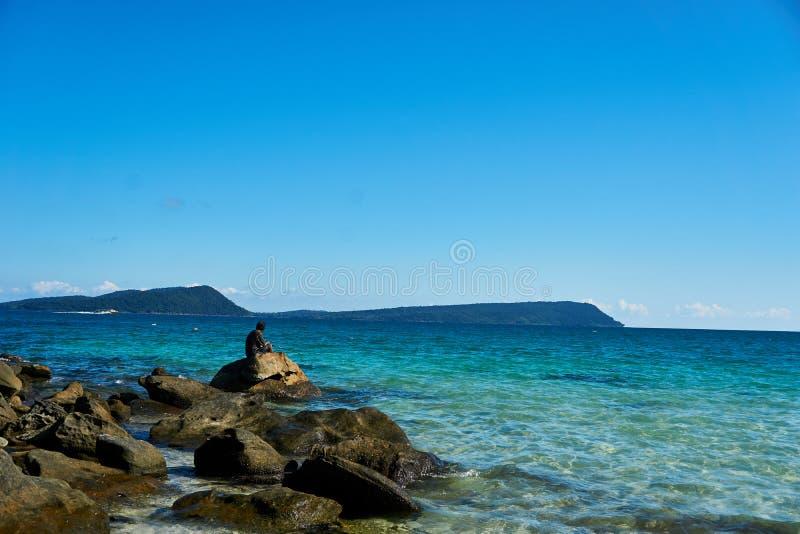 El pescador está pescando en la bahía Camboya del rong de la KOH y se sienta en piedras en la playa imagenes de archivo