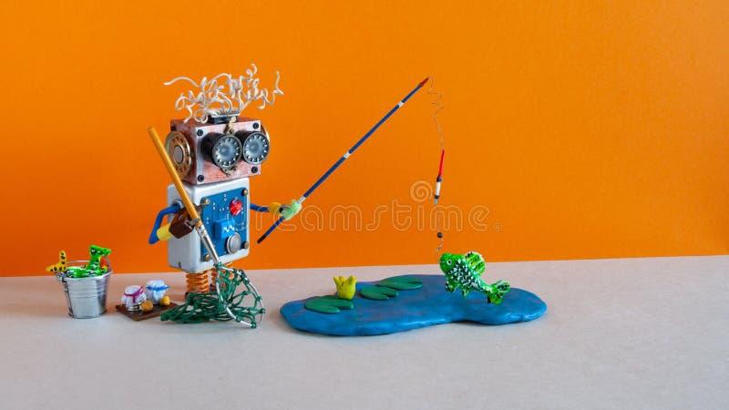 El pescador juguetón atrapó peces gordos Concepto de vacaciones de pesca robótica Gracioso angler con accesorios para el cubo de  foto de archivo