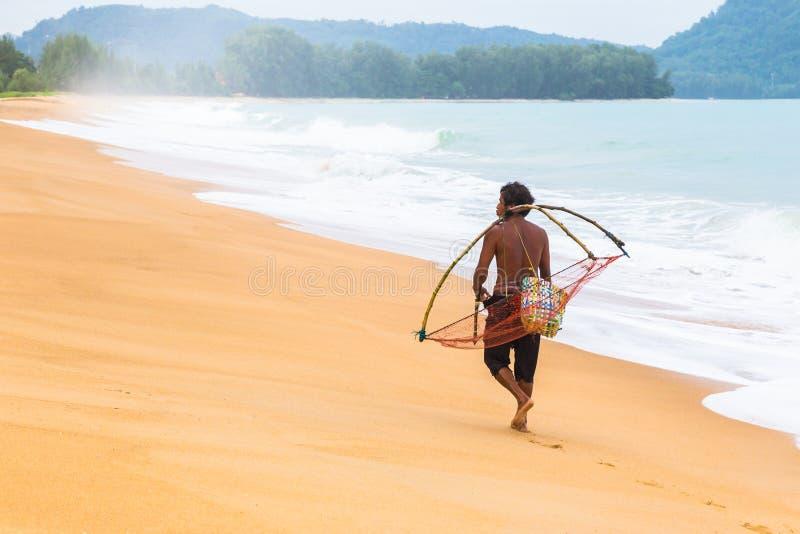 El pescador local camina a casa llevando su herramienta de expediente después de hola imagen de archivo libre de regalías