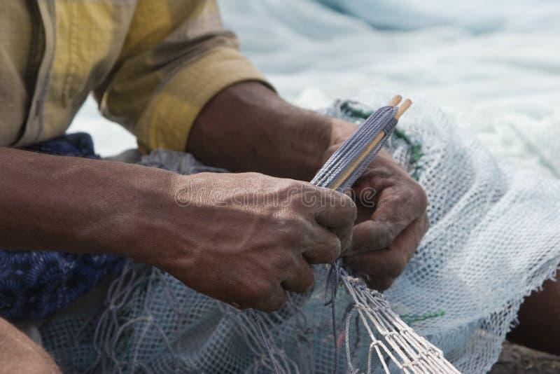 El pescador local de Fudjairah UAE A fija los agujeros y enreda en su red en Fudjairah. fotos de archivo