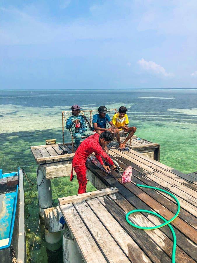El pescador local de maldivo está cortando pescados en el embarcadero fotos de archivo libres de regalías