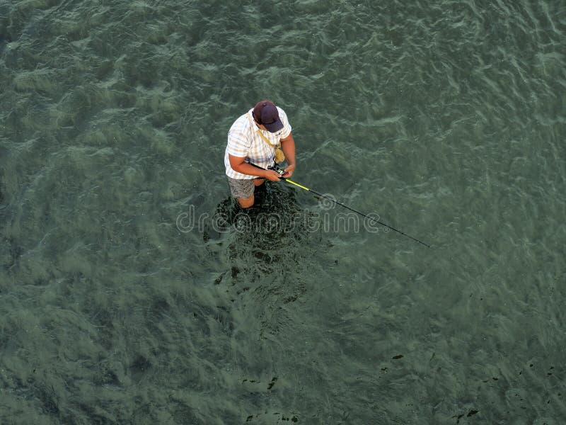 El pescador se coloca en el agua imagen de archivo