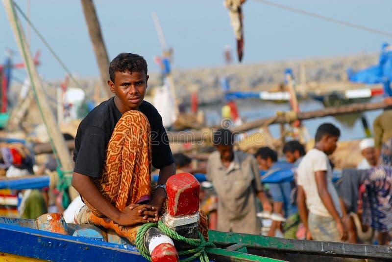 El pescador se sienta en la parte delantera del barco de pesca acaba de llegar al puerto en Al Hudaydah, Yemen imágenes de archivo libres de regalías