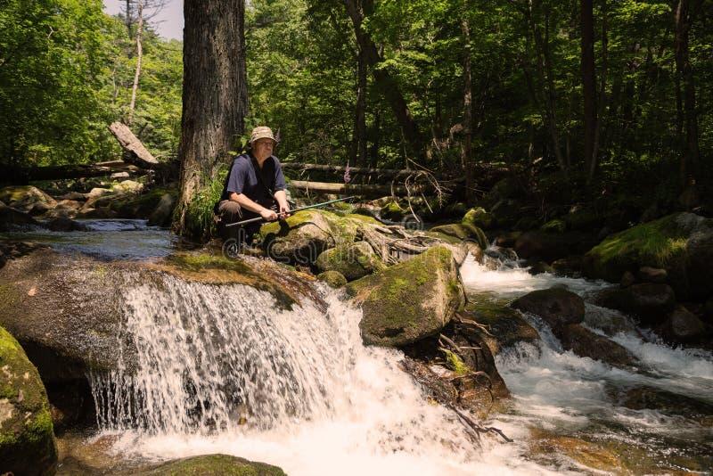 El pescador tiene un resto en el río de la montaña imagenes de archivo