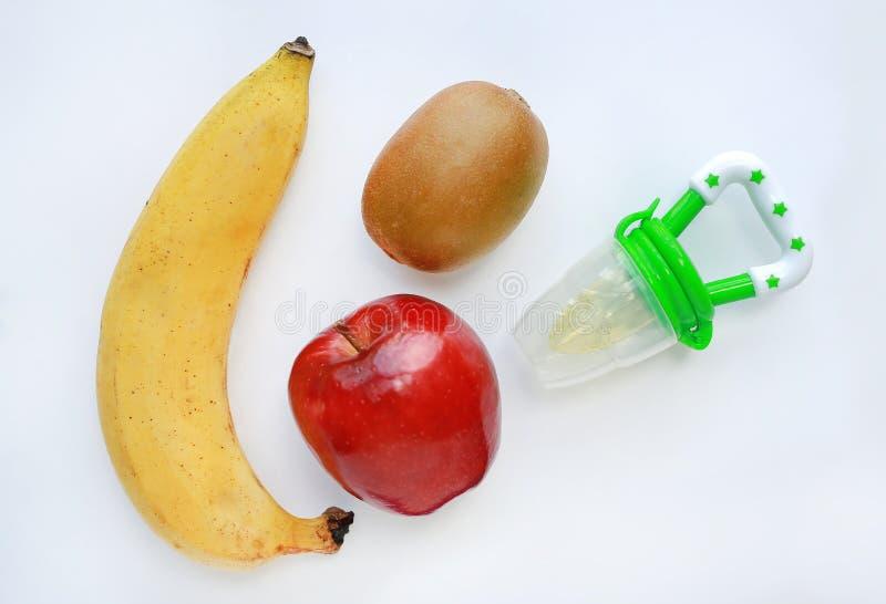 El pezón del bebé y la fruta madura fresca manzana, banana y kiwi sobre fondo blanco foto de archivo