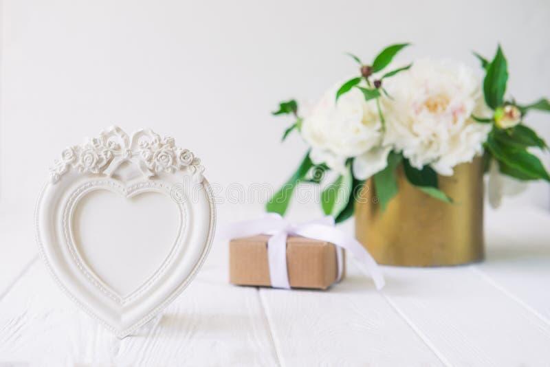 El photoframe en forma de corazón con las flores del yeso, la caja de regalo con la cinta y el vintage ruedan con el ramo blanco  imagen de archivo libre de regalías