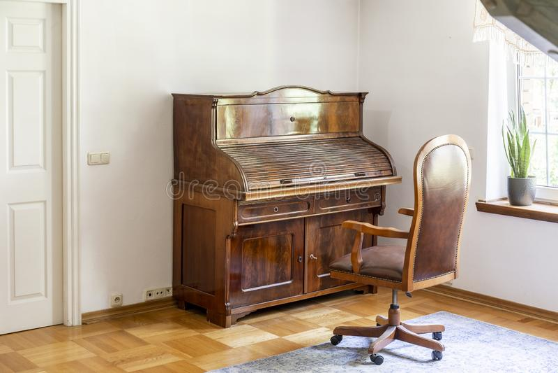 El piano y la silla clásicos encendido rueda adentro un interior antiguo del sitio r fotografía de archivo