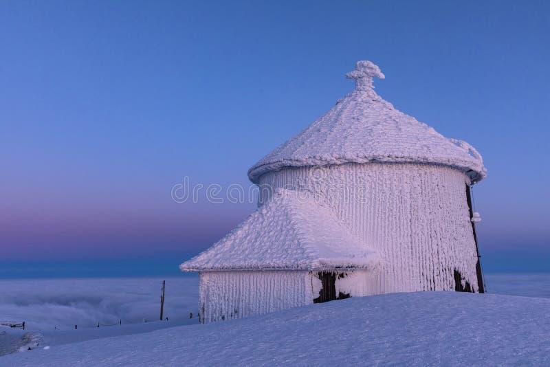 El pico de la montaña de Snezka en invierno en las montañas de Krkonose Snezka después de una puesta del sol teñió en colores en  imagenes de archivo
