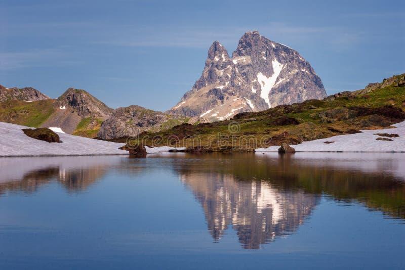 El pico de Ossau del ` de Midi d reflejó en un lago en la nación de los Pirineos foto de archivo libre de regalías