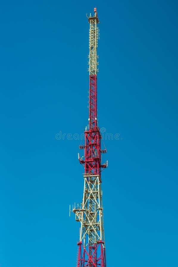 El pico del las telecomunicaciones se eleva contra el cielo azul foto de archivo