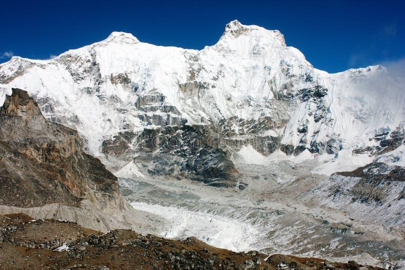 El pico y Chumbu de Hungchhi enarbolan sobre el glaciar de Ngozumba imágenes de archivo libres de regalías