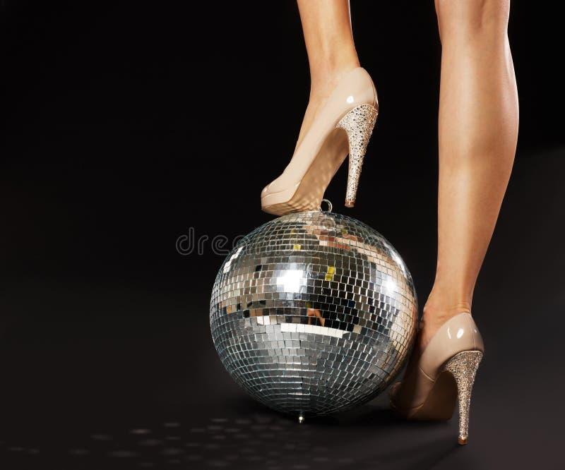 El pie de la mujer sobre la bola de discoteca fotografía de archivo