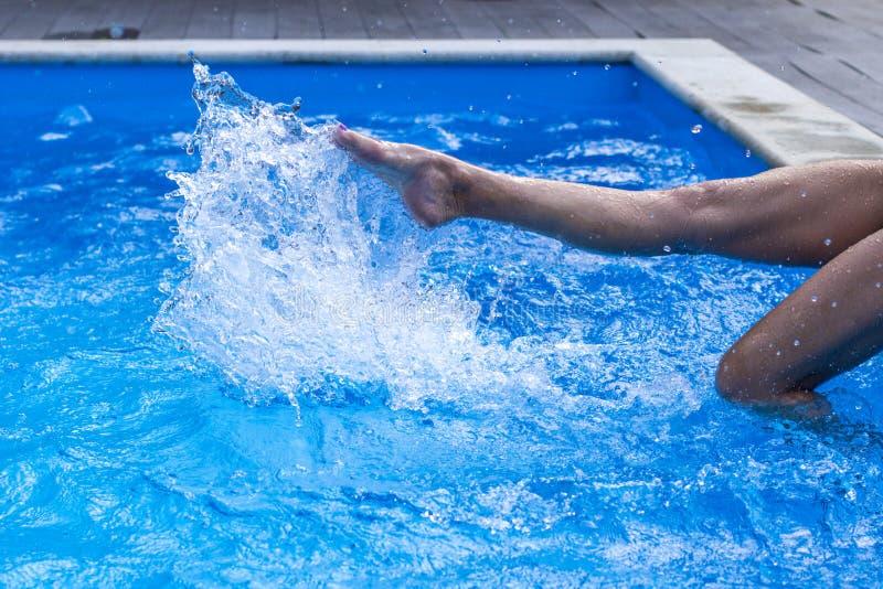 El pie de mujeres jovenes en piscina del agua, salpica de las piernas femeninas fotografía de archivo libre de regalías