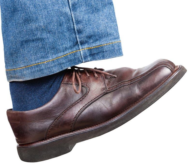 El pie derecho en vaqueros y zapato marrón toma una medida imagenes de archivo