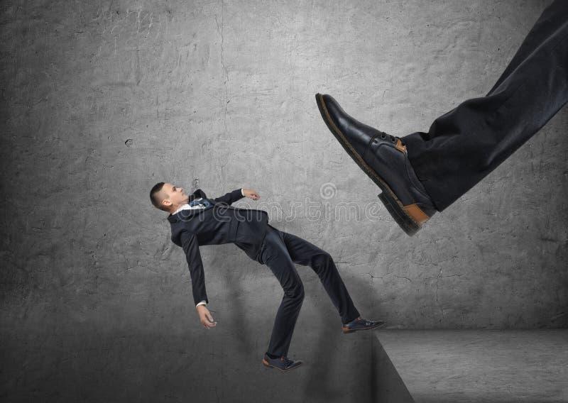 El pie gigante en el zapato negro que golpea a pequeños hombres de negocios con el pie el borde, y de él está cayendo abajo foto de archivo libre de regalías