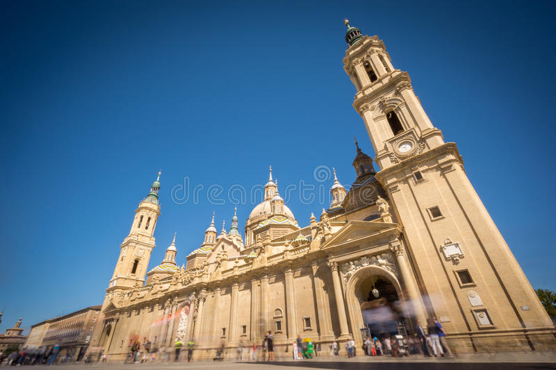 El Pilar basilica wide angle with blurred tourists. Wide angle view of El Pilar basilica, long exposure with blurred tourists and blue sky stock images