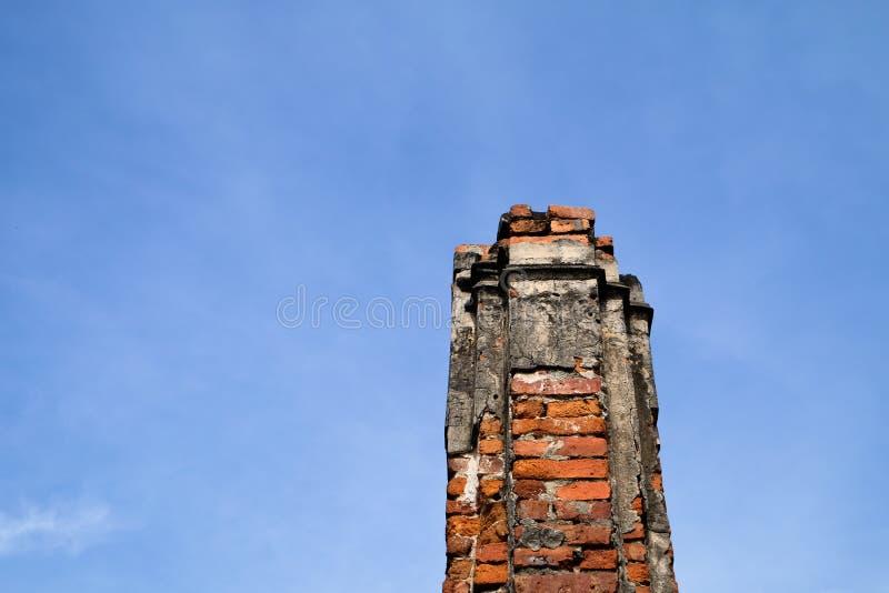 El pilar viejo de los ladrillos con el cielo azul imagenes de archivo