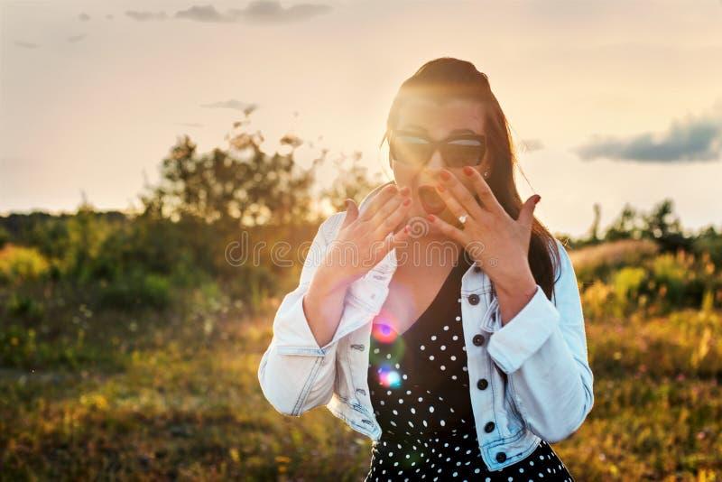 El Pin encima de la muchacha se sorprende con una boca abierta en los rayos de la puesta del sol imagen de archivo