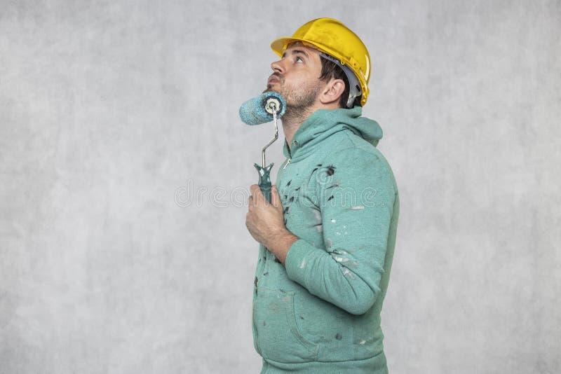 El pintor apoya su barba con un rollo de pintura fotografía de archivo