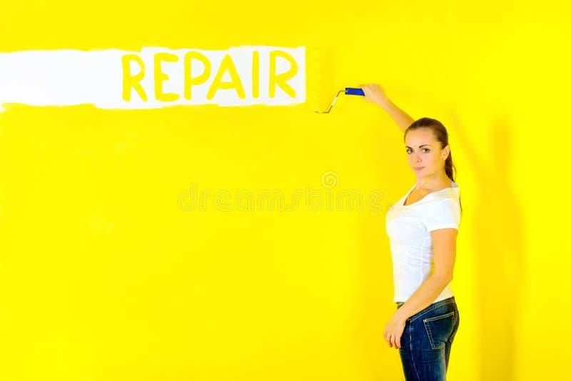 El pintor de la muchacha pinta la pared con un rodillo fotos de archivo