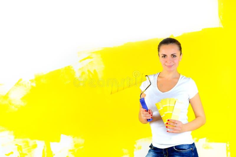 El pintor de la muchacha sostiene un rodillo en sus manos y elige un color imagenes de archivo