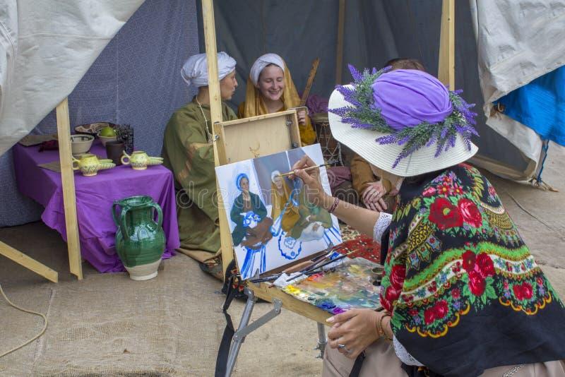 El pintor de la mujer en un sombrero de la lavanda dibuja en la gente de la lona que se sienta en una carpa azul vieja festival fotografía de archivo libre de regalías