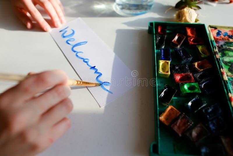 El pintor de la mujer joven escribe la escritura en el papel, sentada de la acuarela imagen de archivo