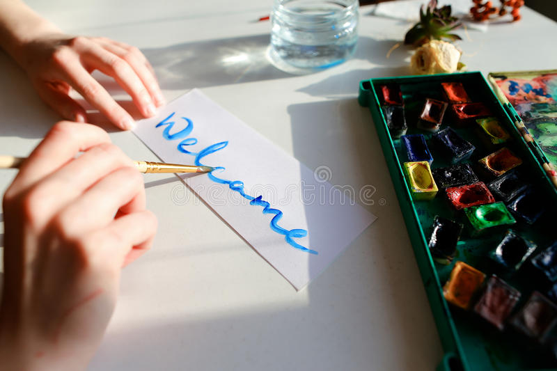 El pintor de la mujer joven escribe la escritura en el papel, sentada de la acuarela foto de archivo libre de regalías