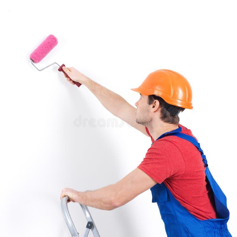 El pintor del artesano se coloca en las escaleras con el rodillo foto de archivo