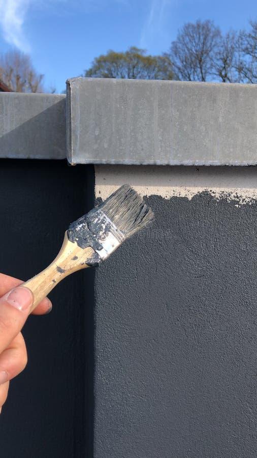El pintor pinta la fachada imagen de archivo