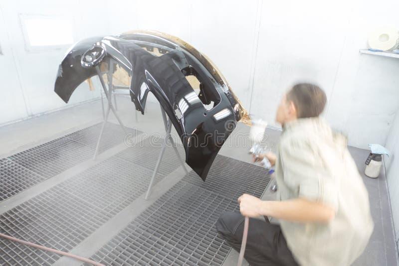 El pintor pinta un coche de parachoques imagenes de archivo